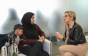 Marilena Di Coste discussing with mother and child during meeting